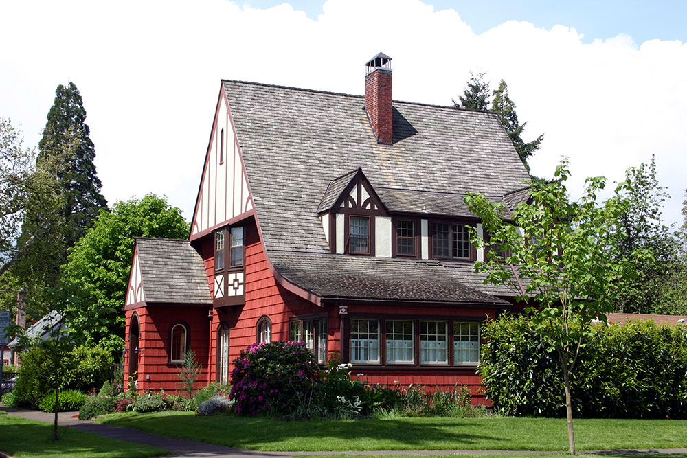 A nice looking but modest midwestern house with red siding and a gray roof