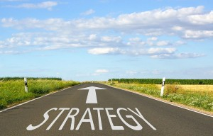 An arrow in the road pointing forward with the word Strategy