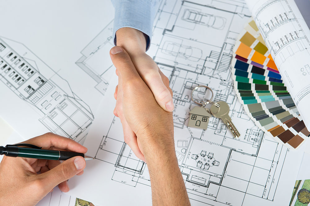 overhead shot of two hands shaken with a pen in another above a lot of floorplans and house keys