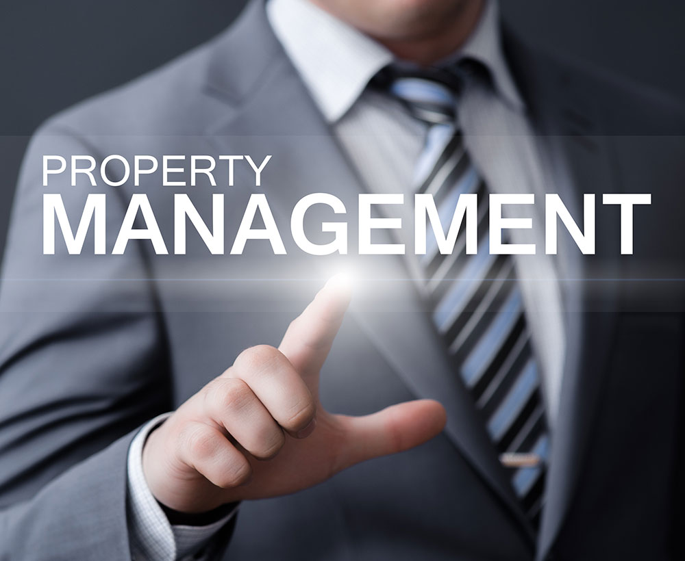 man in suit behind a property management label