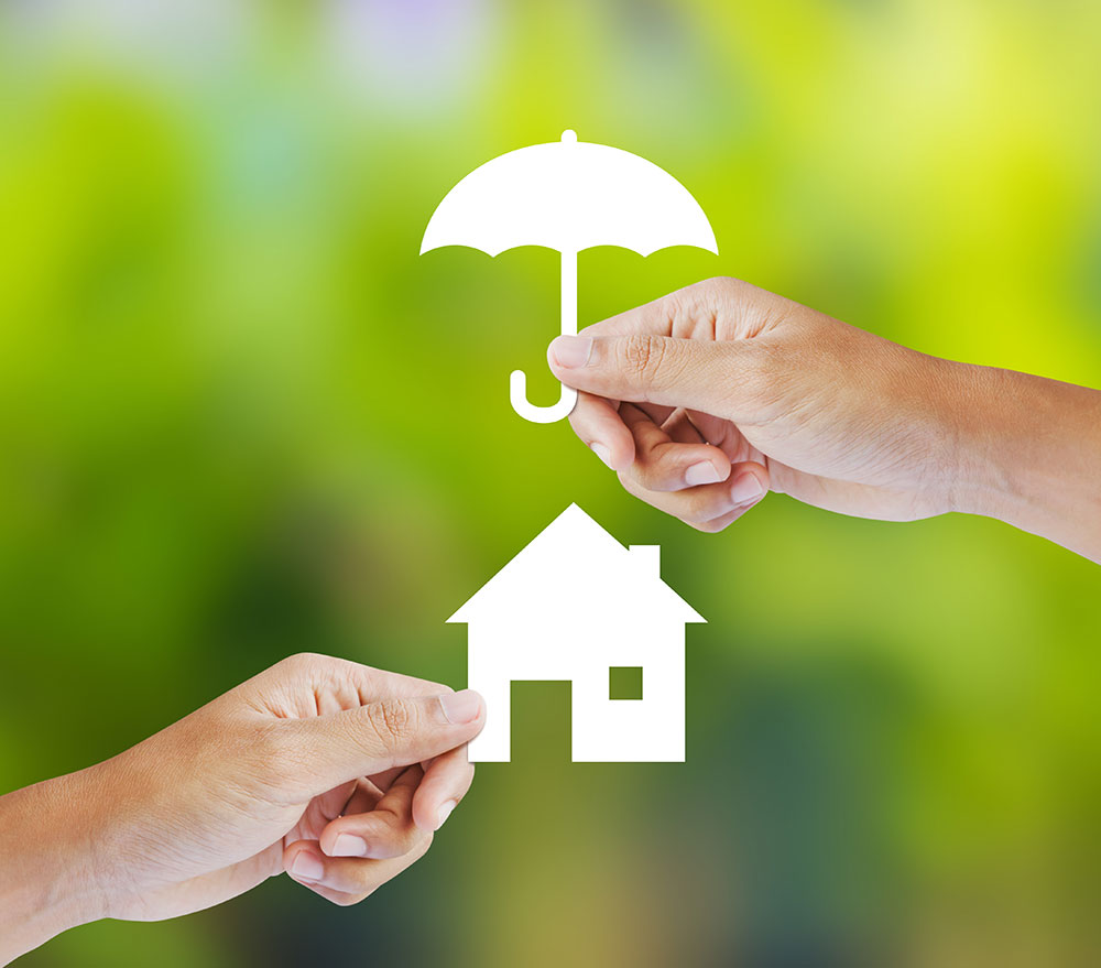 a hand holding a paper cutout of an umbrella over a cutout of a house to illustrate property management